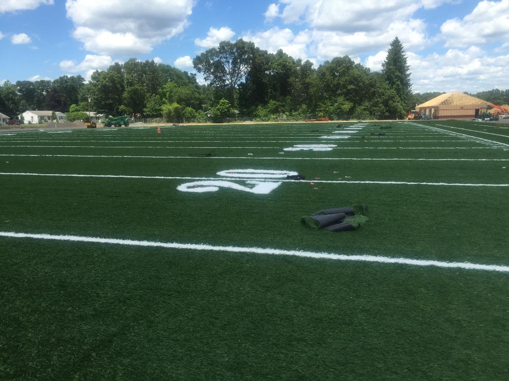 Artificial turf football yard lines and numbers being installed