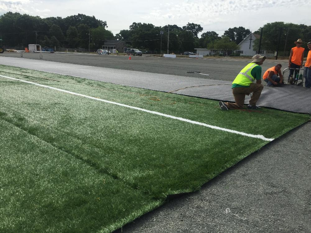 Men working on artificial turf infield