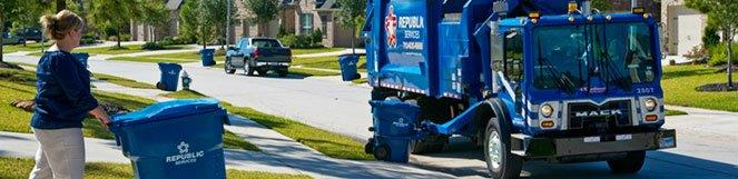 Person pushing their trash cart to the curb where an automated trash truck is ready to pick it up